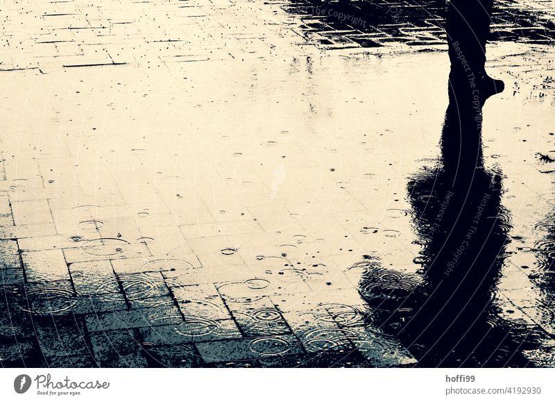 abstrakte Regenpfütze mit Mensch Pfütze Pfützenspiegelung Pfützenbild pladdern Regentropfen schlechtes Wetter Wassertropfen Natur Tropfen nass Pflastersteine