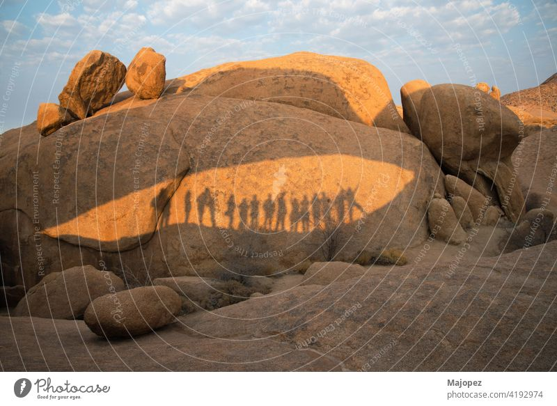 Felsen im Damaraland mit den Schatten einer Gruppe von Menschen an einem sonnigen Tag Namibia damaraland Menschengruppe genießen Glück Zusammensein wüst heiß