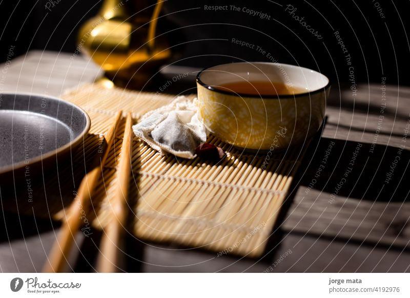 Dunkler Tee Hintergrund mit Tasse heißem Tee auf dem Tisch. chinesischer Tee China Medizin Tee - Heißgetränk Teezeremonie Teekocher