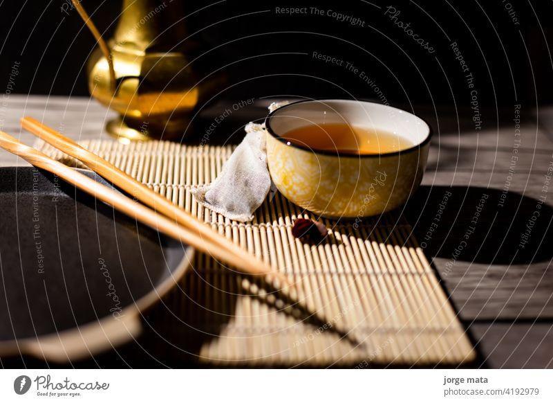 Dunkler Tee-Hintergrund mit Tasse heißem Tee auf dem Tisch. Kopierbereich für Ihr Design. Authentischer Vintage-Stil. Traditionelle Teezeremonie Anordnung