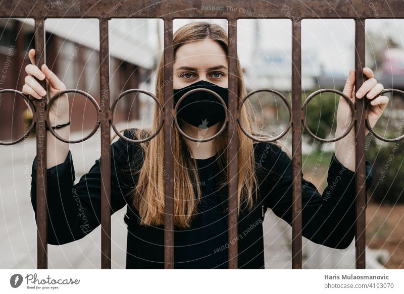 Frau mit Gesichtsmaske hinter den Gittern im Freien, Konzept Lockdown Covid 19 Erwachsener allein Käfig Korona Corona-Virus Coronavirus COVID Covid-Sperre