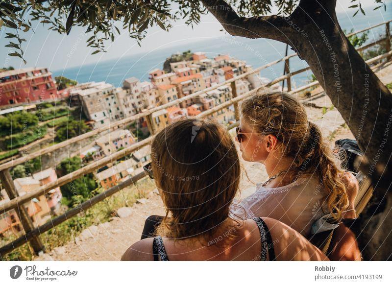 Zwei junge Frauen unterm Olivenbaum mit Blick auf Manarola blond Sonne Sonnenlicht Baum Portrait lächeln schön hübsch Urlaub Sommer Sommerfeeling Außenaufnahme