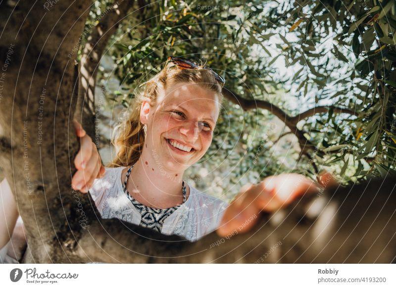 Lächelnde junge Frau unterm Olivenbaum blond Sonne Sonnenlicht Baum Portrait lächeln schön hübsch Urlaub Sommer Sommerfeeling Außenaufnahme Farbfoto Freude