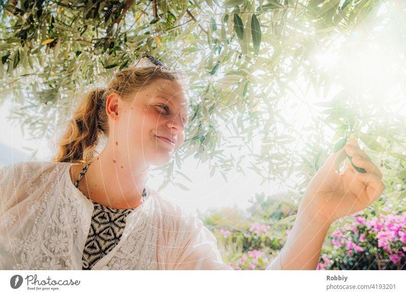 Junge Frau unterm Olivenbaum bei Sonnenschein junge Frau blond Sonnenlicht Baum Gegenlicht Portrait lächeln schön hübsch Urlaub Sommer Sommerfeeling