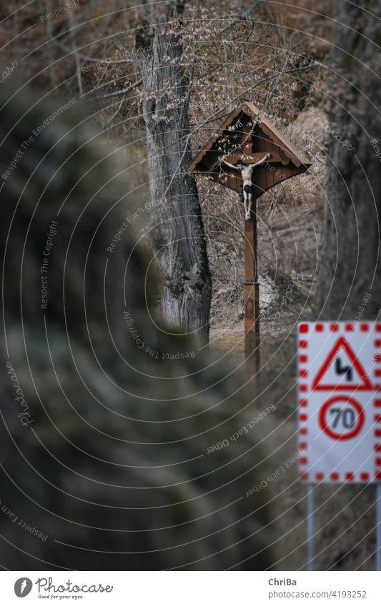 Warnschild und Wegekreuz an einer Motorradstrecke auf der schwäbischen Alb symbol road warning danger traffic caution sign drive accident roadsign beware