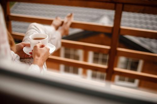 Junge Frau in stilvoller Nachtwäsche trinkt morgens gerne Kaffee oder Tee im Freien auf dem Balkon und schaut auf die Berge. trinken Mädchen Morgen Beteiligung