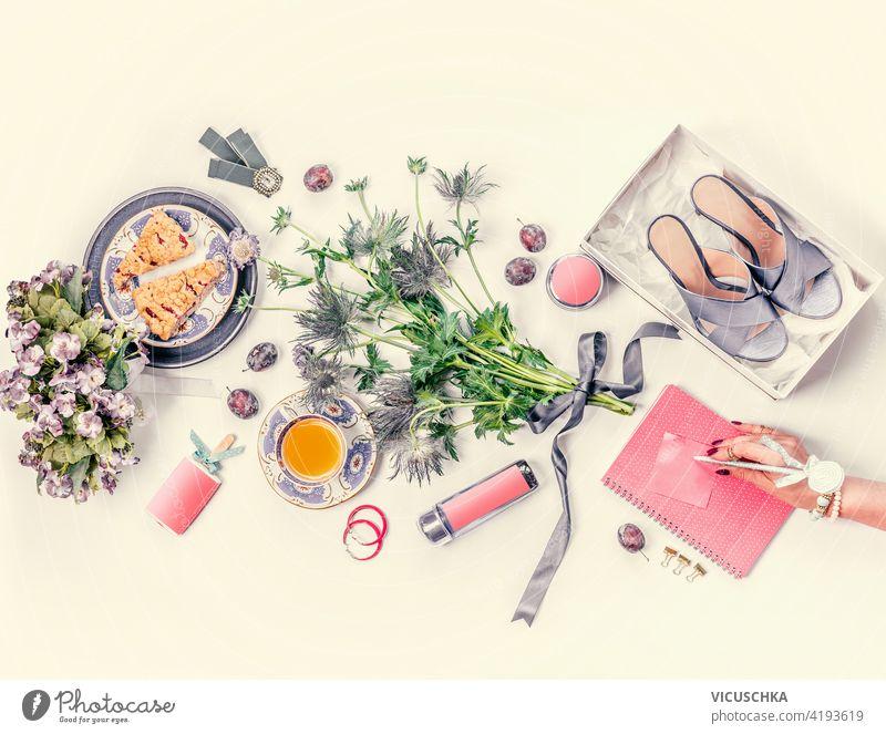 Frauen Hand mit rosa Notebook Lebensstil flach lag mit blauen neuen High Heels Schuhe in der Box, Blumenstrauß, Tasse Tee, Kuchen, Schmuck, Kosmetik, Früchte auf weißem Schreibtisch. Ansicht von oben. Schönheit und Mode