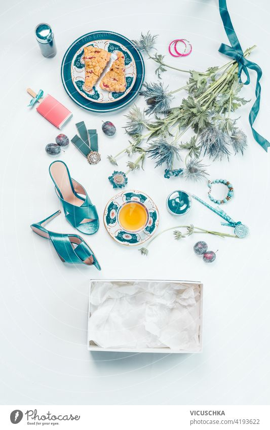 Weiblicher Lebensstil flach lag mit blauen neuen High Heels Schuhe, Blumenstrauß, eine Tasse Tee, Kuchen, Schmuck, Kosmetika, leere Box, Früchte auf weißem Schreibtisch . Ansicht von oben. Schönheit und Mode Konzept