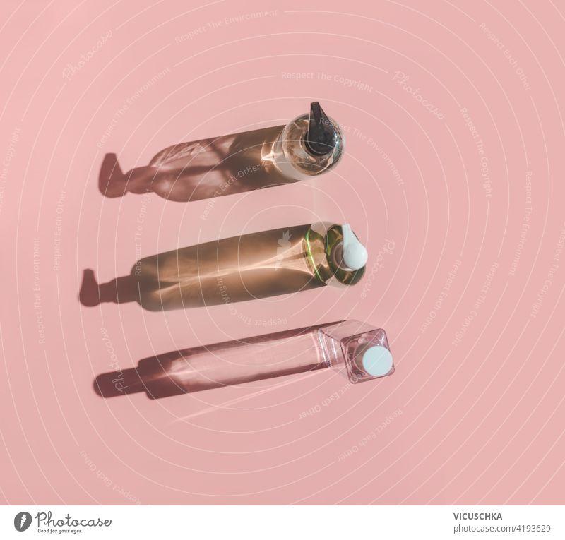 Drei Kosmetikflaschen im Sonnenlicht mit Schatten auf rosa Hintergrund. Ansicht von oben drei Produkt Flaschen Draufsicht Schönheit Pflege Essenz Mode Reichtum