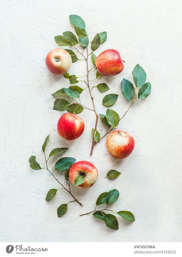 Komposition von frischen roten Äpfeln mit grünen Blättern auf weißem Schreibtisch-Hintergrund. Ansicht von oben. Flach legen Zusammensetzung Draufsicht