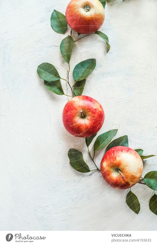 Frische rote Äpfel mit grünen Blättern auf weißem Schreibtischhintergrund. Ansicht von oben frisch Hintergrund Draufsicht Frucht sehr wenige Ernährung Vitamin