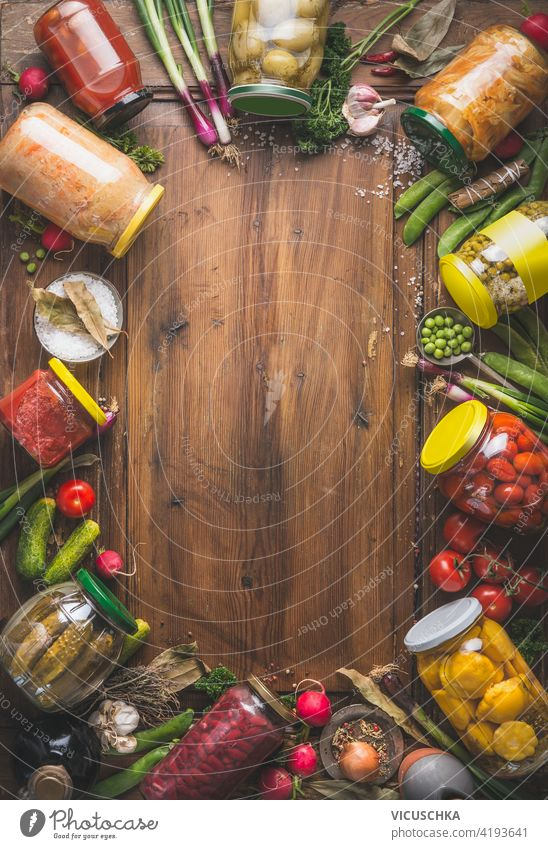 Rahmen von verschiedenen eingelegten bunten Gemüse in Gläsern auf hölzernen Hintergrund mit Zutaten, Kräuter und Gewürze. Ansicht von oben. Platz zum Kopieren. Mock up. Ernte einmachen. Fermentierte Lebensmittel. Gemüsekonserven