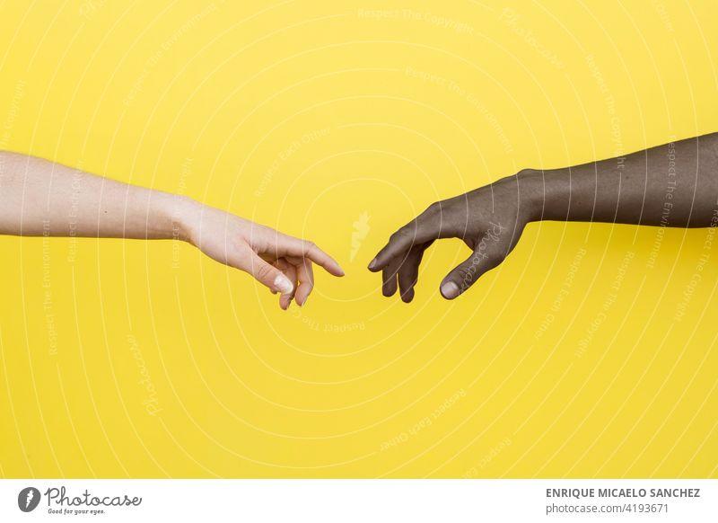 Weiße Hand und schwarze Hand über zu berühren auf gelbem Hintergrund Menschen Freundschaft Zusammensein umklammert Afrikanisch international Partnerschaft Haut