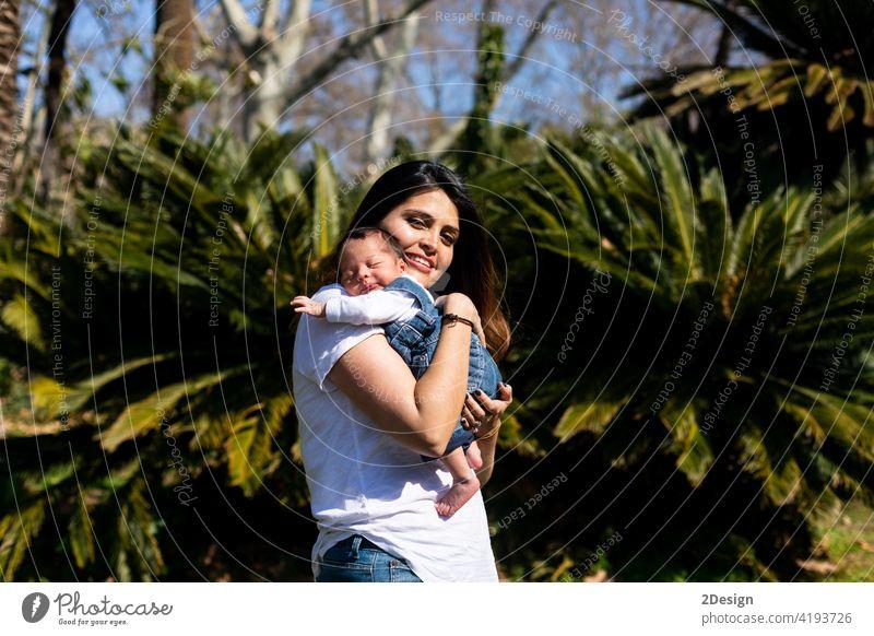 Liebevolle Mutter mit ihrem neugeborenen Baby auf dem Arm. Kind im Freien Person Familie Beteiligung Frau Lifestyle Mama Mutterschaft Eltern schön Arme Säugling