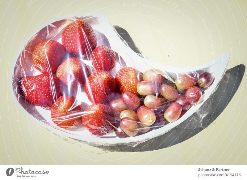 In Frischhaltefolie verpackte Erdbeeren und Trauben Obst Buffet Fructose Früchte natürlich unnatürlich schwitzen Lebensmittel Frucht frisch Ernährung süß