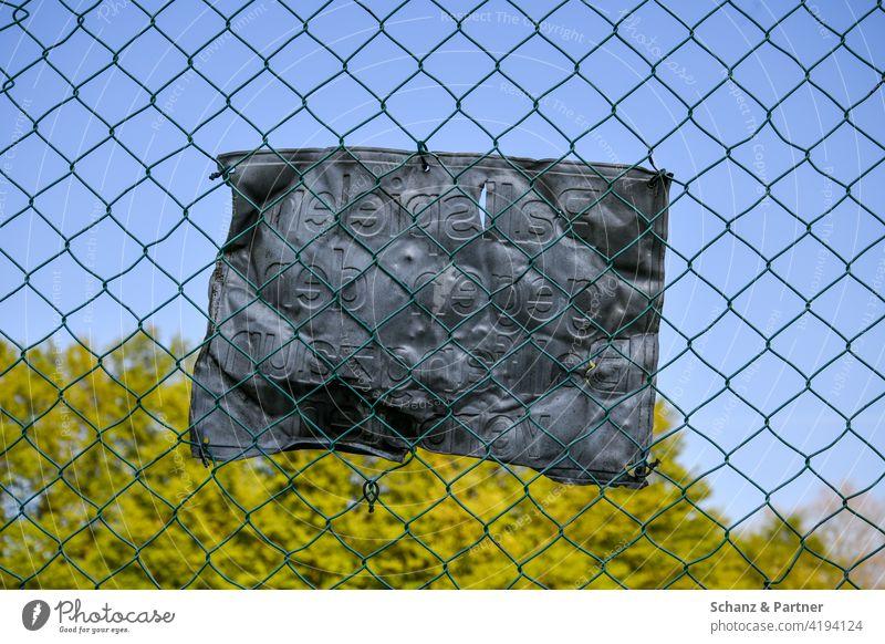 verbeultes Blechschild am Maschendrahtzaun Zaun Schild Hinweisschild Warnhinweis misachten Misachtung verboten Bolzplatz Bäume verbogen Vandalismus