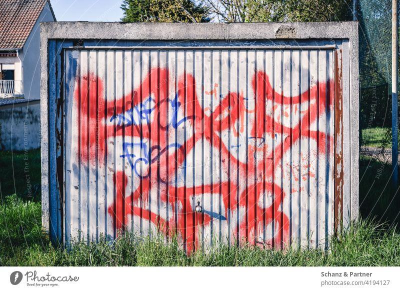 mit Graffiti besprühtes Garagentor einer Fertiggarage Eingang rot zugewachsen Beton Tags Blech vergessen verwittert Geheimnis Tor geschlossen Einfahrt verrostet