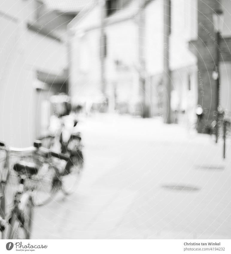 Leere Fußgängerzone in der Innenstadt mit abgestellten Fahrrädern. Schwarzweiß und unscharf. leer Menschenleer Gebäude Geschäfte Architektur Stadt Fassade