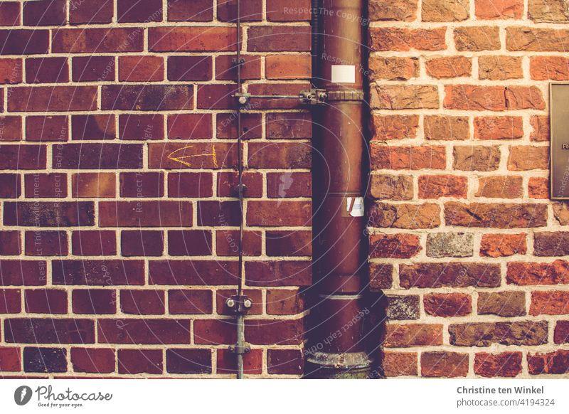Ein Fallrohr und ein Blitzableiter in der Wand am Übergang zwischen zwei Backsteinmauern an einem alten Gebäude Backsteinwand Mauer Fassade Backsteinfassade