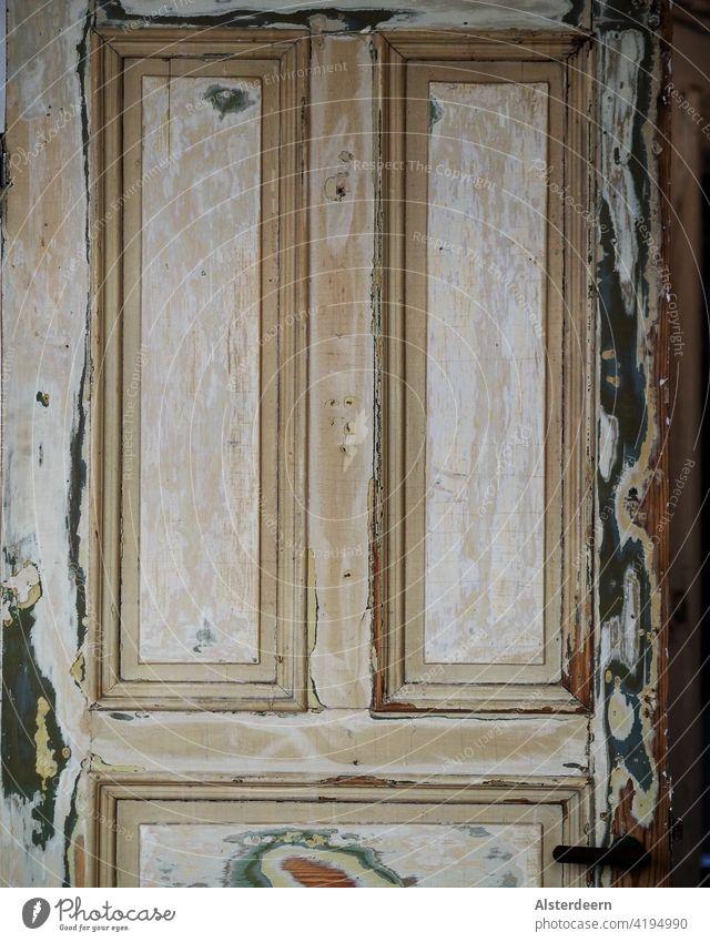 Obere Hälfte einer alten Tür in einer Altbauwohnung die viele Schichten Farbe hat, abgeschliffen wurde jedoch noch nicht neu lackiert der Türgriff ist zu sehen