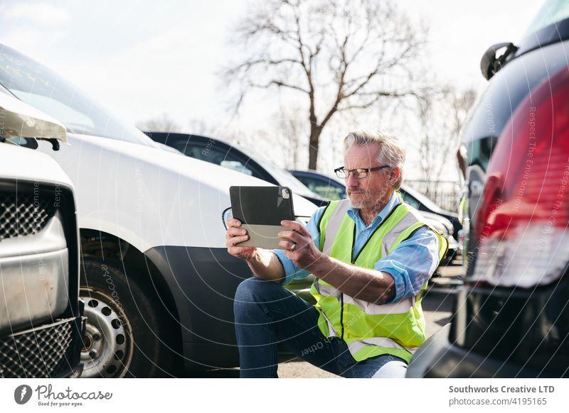 Männlicher Schadensregulierer, der ein Foto auf einem digitalen Tablet macht, um einen Versicherungsanspruch im Auto zu bewerten PKW Unfall Schiffswrack Absturz