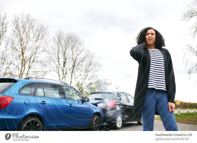 Weiblicher Fahrer mit Schleudertrauma-Verletzung, der nach einem Verkehrsunfall neben dem beschädigten Auto steht Frau PKW Unfall Schiffswrack Absturz verletzt