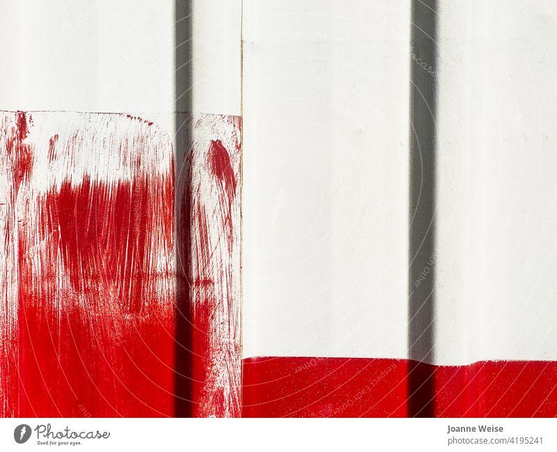 Weiße Wand mit leuchtend roten Farbpinselstrichen. weiße Wand rot und weiß rote Farbe Außenaufnahme Farbfoto Fassade Gebäude Tag Detailaufnahme Pinselstrich