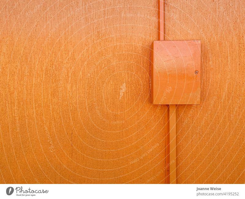 Orangefarbene Wand mit Kasten. orange Farbfoto Außenaufnahme Textfreiraum links Textfreiraum oben Tag leuchtende Farben orangefarbene Wand Gebäude Fassade bunt