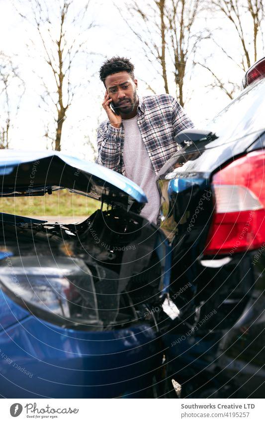 Junger männlicher Fahrer, der nach einem Verkehrsunfall die Autoversicherung per Mobiltelefon anruft Mann PKW Unfall Schiffswrack Absturz Versicherung Anspruch