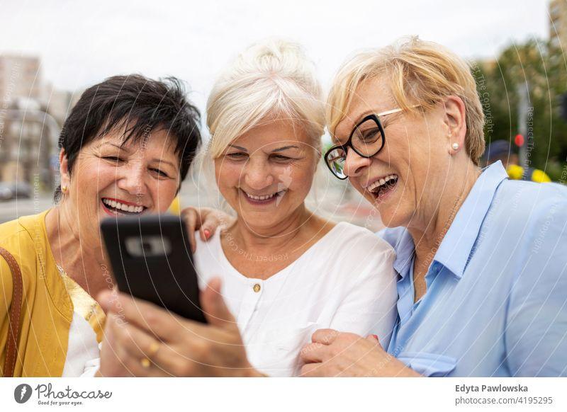 Gruppe älterer Frauen, die gemeinsam ein Smartphone benutzen Senior Menschen in den Ruhestand getreten Großmutter Freizeit Stehen selbstbewusst attraktiv urban