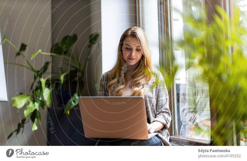 Junge Geschäftsfrau mit Laptop in ihrem Büro Frau Mädchen Menschen Unternehmer Business gelungen Erfolg professionell jung Erwachsener Lifestyle im Innenbereich