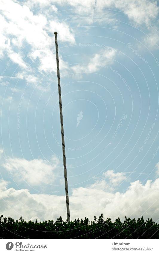 Eine Fahnenstange mit Schlagseite Flaggenstock verziert geschmückt schief Himmel Wolken schönes Wetter Gebüsch Grünzeug Außenaufnahme Menschenleer Tag Farbfoto