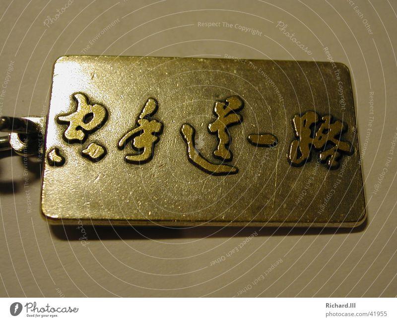 Karate Schriftzeichen Objektfotografie Schmuckanhänger Plakette Vor hellem Hintergrund