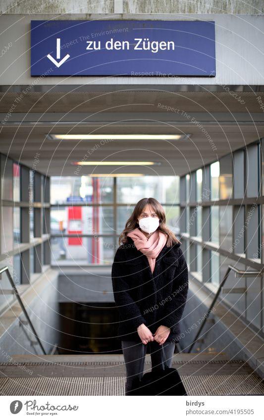 Eine junge Frau mit FFP2 - Maske steht am Bahnhof vor der Treppe zu den Gleisen, Zügen. Maskenpflicht Deutsche Bundesbahn DB Pandemie covid-19 Coronavirus