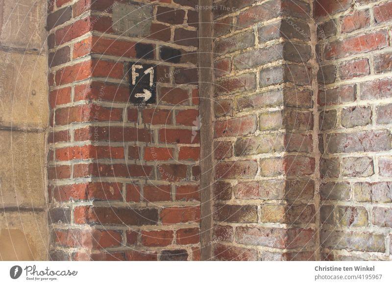 Wegweiser F1 mit Pfeil nach rechts in der Ecke eines Gebäudes, in der mehrere alte Backstein- und Sandsteinmauern aufeinander treffen Schild