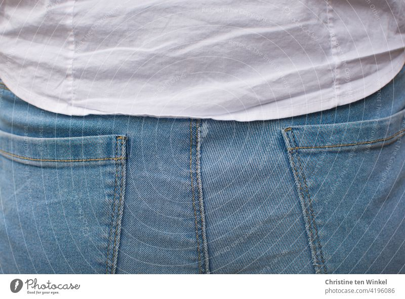 Rückansicht einer jungen Frau in hellblauer Jeans und weißer Bluse. Detailaufnahme. Popo Jeanspo Rücken Erwachsene 1 Jugendliche Junge Frau 18-30 Jahre Mensch