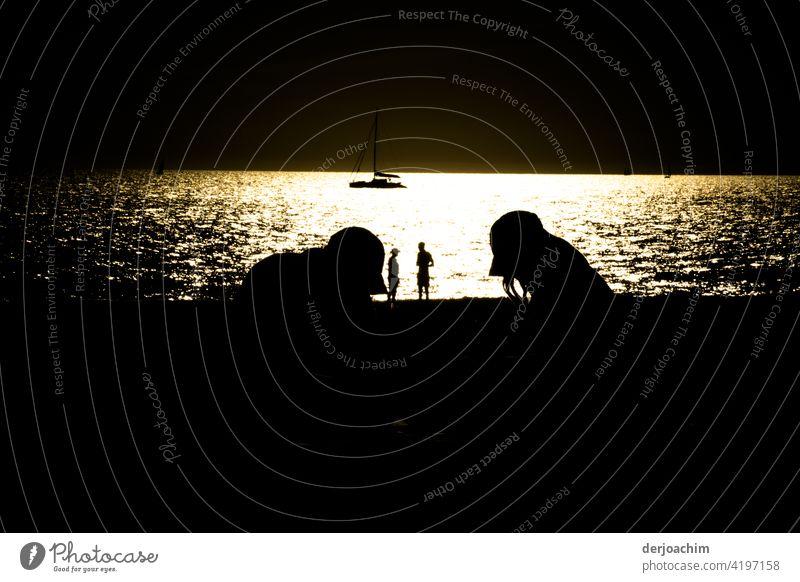 Das letzte Tageslicht. Das Boot liegt vor Anker. Ein paar Figuren am Strand laufen hin und her. Zwei Möven betrachten das ganze  von der Mauer. Das Meer schimmert  golden.