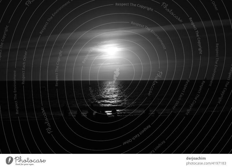 Gleich ist es Dunkel in Süd Australia am Strand von Adelaide. Nur Wasser, Himmel und die Sonne sowie ein paar Schatten von Figuren am Meer. Küstenstreifen Natur