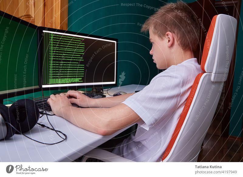 Ein junger Programmierer druckt den Programmcode auf dem Computerbildschirm aus. Das Konzept der Computersicherheit, Technologieentwicklung und junge Fachkräfte