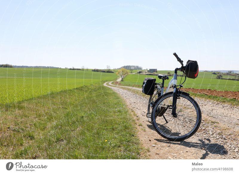 Frühlingslandschaft mit einem E-Bike auf dem Weg Fahrrad elektrisch Biker Abend Landschaft Freizeit Natur im Freien Erholung Himmel Sport Sommer Abenteuer