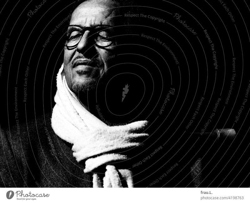 Ein alter Mann genießt die Sonne Sonnenschein Jacke Blazer Porträt Gesicht Brille Winter Frühling Schal