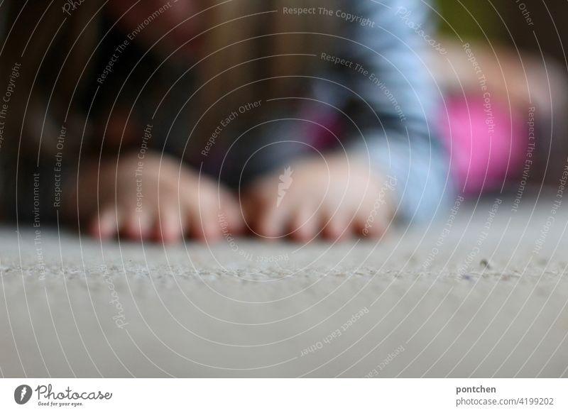 Kind spielt am Boden. Unscharfe Kinderhände liegen teppich kind spielen unschärfe häusliches leben Leben krabbeln