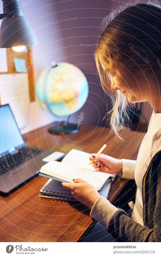 Studentin, die von zu Hause aus lernt. Junge Frau hat Unterricht online, macht Notizen, liest und lernt am Schreibtisch sitzend Bildung im Innenbereich Lernen
