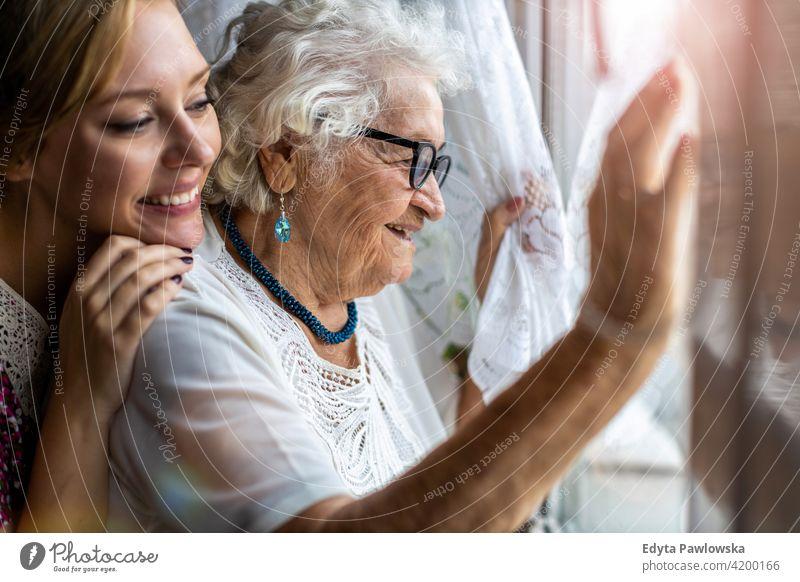 Junge Frau verbringt Zeit mit ihrer älteren Großmutter zu Hause Menschen Senior reif lässig Kaukasier heimwärts alt Alterung häusliches Leben Rentnerin