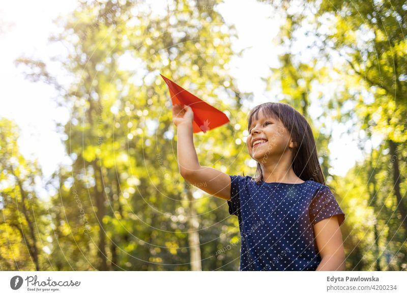 Kleines Mädchen spielt mit Papier Flugzeug im Park Menschen Kind kleines Mädchen Kinder Kindheit im Freien lässig niedlich schön Porträt Lifestyle elementar