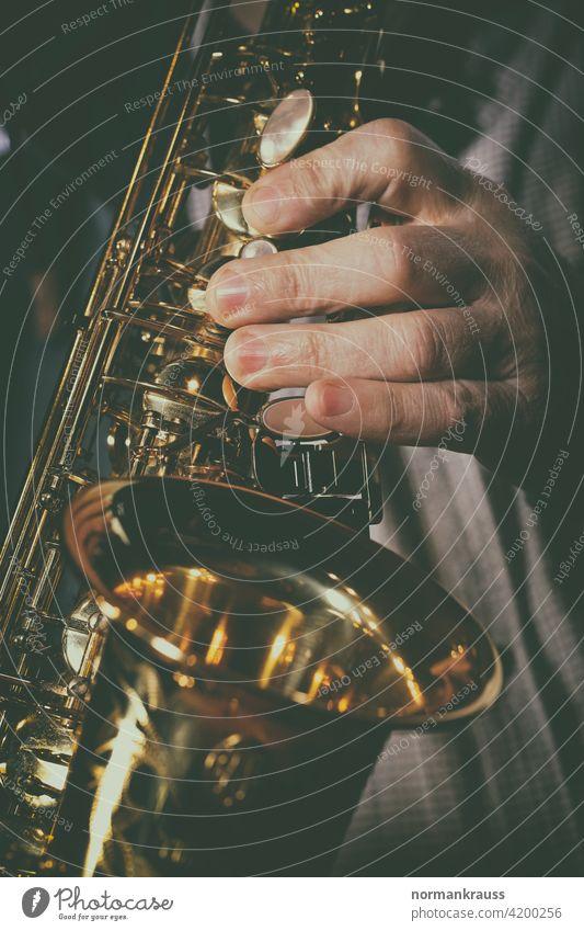 Saxofon und Musiker saxophon hand finger musikinstrument blasinstrument musiker glanz gold messing holzblasinstrument musikant