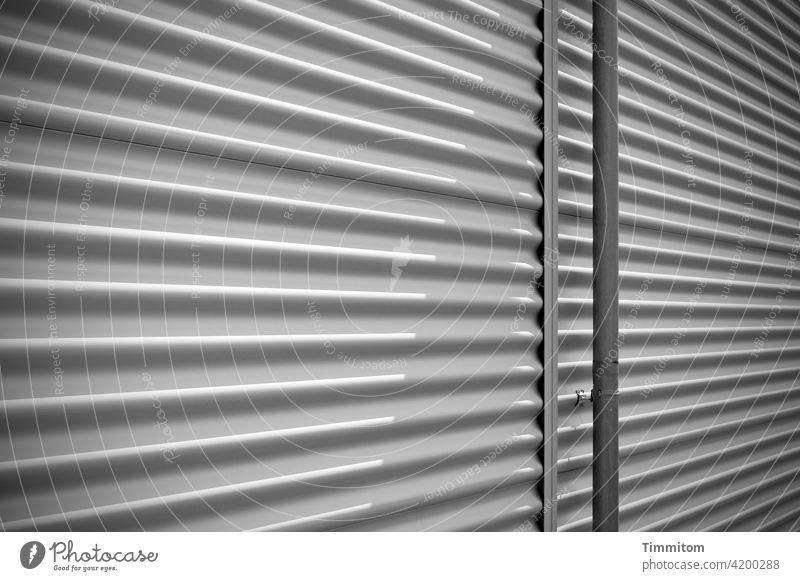 Eine eher sachliche Fassadengestaltung Gebäude Gebäudefassade Fallrohr Metall Design Gestaltung Linien Licht und Schatten Architektur