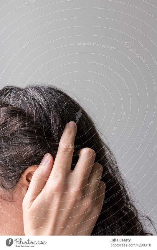 Frau, die ihr Haar selbstbewusst anfasst; natürliches graues Haar wächst heraus Behaarung Haarpflege wachsen auswachsen Farbstoff farbstofffrei Quarantäne