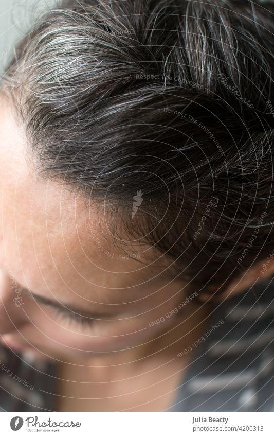Oberseite des Kopfes einer Frau: graue Haare wachsen ein Behaarung Haarpflege natürlich auswachsen Farbstoff farbstofffrei Quarantäne Silber frisch 40 Jahre alt