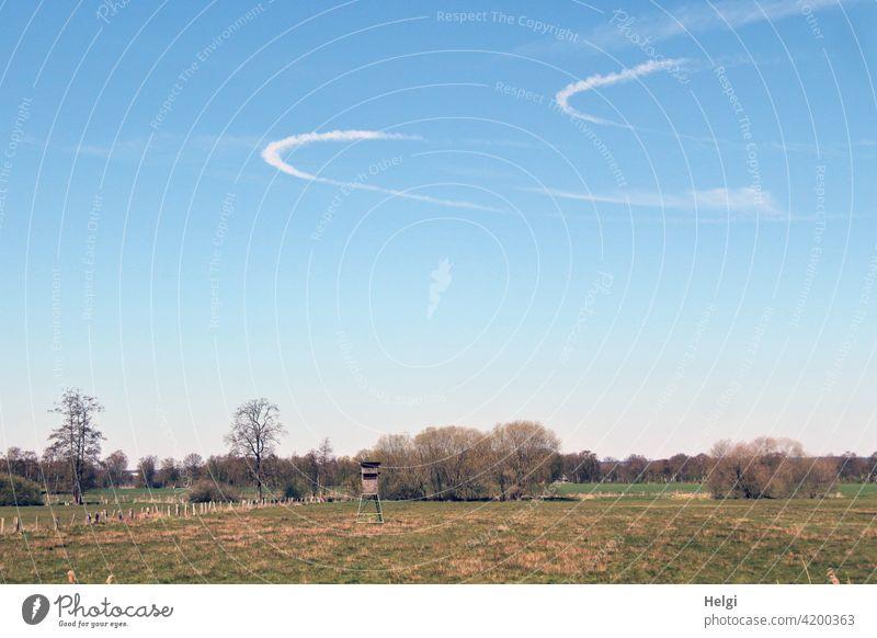zwei bogenförmige Kondensstreifen am blauen Himmel über einer Wiese mit Hochsitz und Bäumen Landschaft Natur Spuren Frühling Umwelt Weide menschenleer